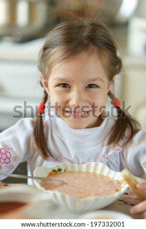 Little girl eating soup at table at home