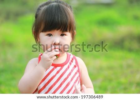 Little girl eating strawberries  - stock photo