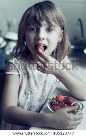Little girl eating strawberry - stock photo