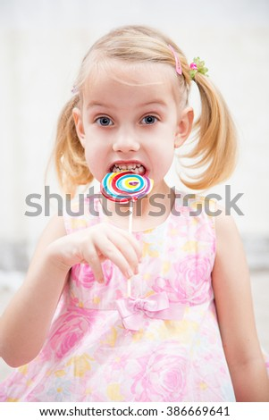 little girl eating sugar candy - stock photo