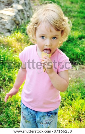 little girl eating sweet ice cream outdoors - stock photo