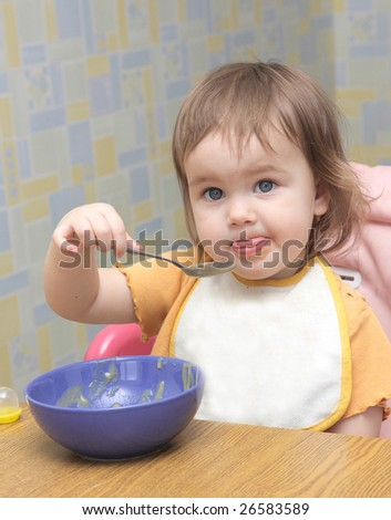 little girl eating with spoon - stock photo