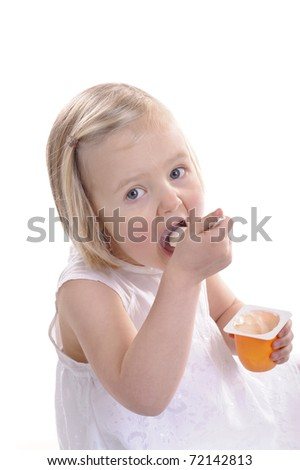 little girl eating youghurt, mouth wide open. isolated on white