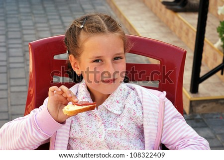 Little girl eats a sandwich outdoors