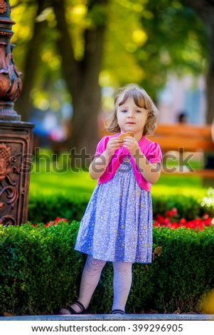 Little girl eats cookies in the park. Summer - stock photo