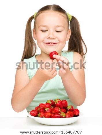 Little girl eats strawberries, isolated over white - stock photo
