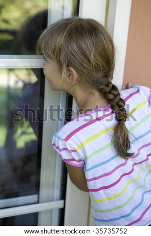 little girl eight years old look through window