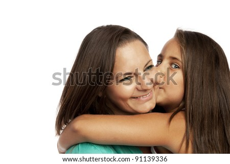 Little girl embracing and kissing her mother - stock photo