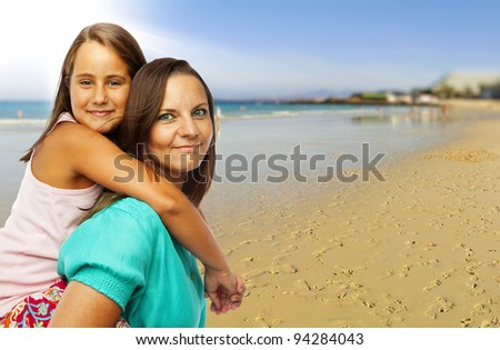 Little girl embracing her mother at the beach - stock photo