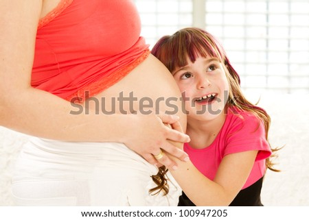 Little girl embracing her pregnant mother