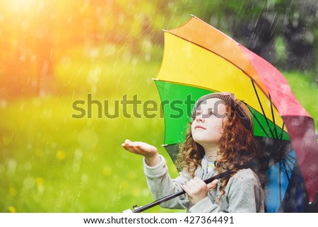 Little girl enjoy to spring rain.  - stock photo