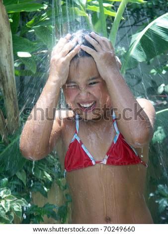 Little girl enjoying an outside shower. - stock photo