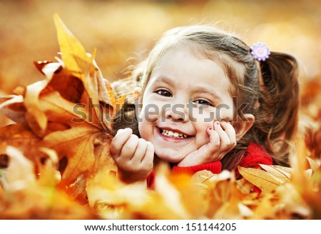 Little girl enjoying autumn in the park - stock photo
