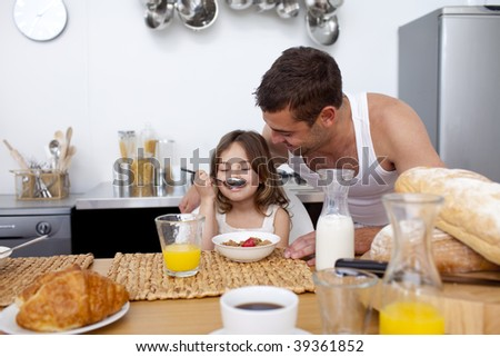 Little girl enjoying her breakfast with her father in kitchen