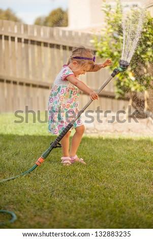 Little girl enjoying herself in the spray - stock photo