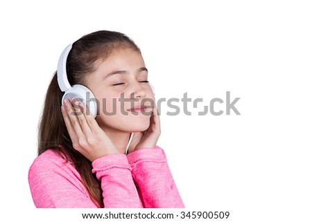 Little girl enjoying music in headphones at home relaxing. Relaxed little girl listening to music with earphones with eyes closed looking serene and happy. - stock photo