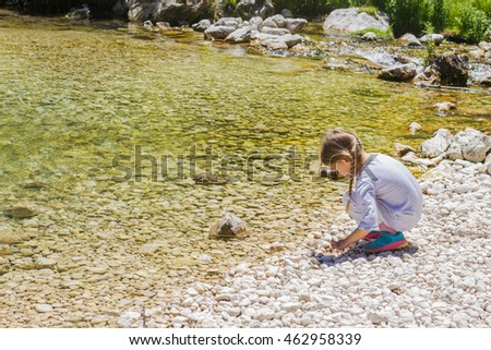 Little girl enjoying nature near spring creek water.