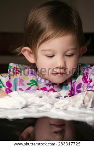 Little girl enjoying playing with foamy cream - stock photo
