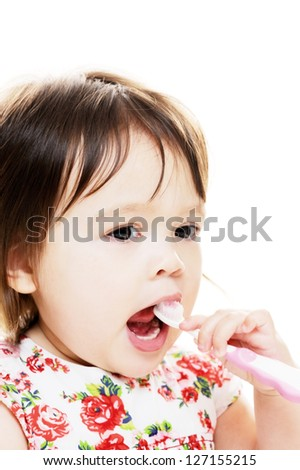 Little girl enjoys brushing her teeth - stock photo