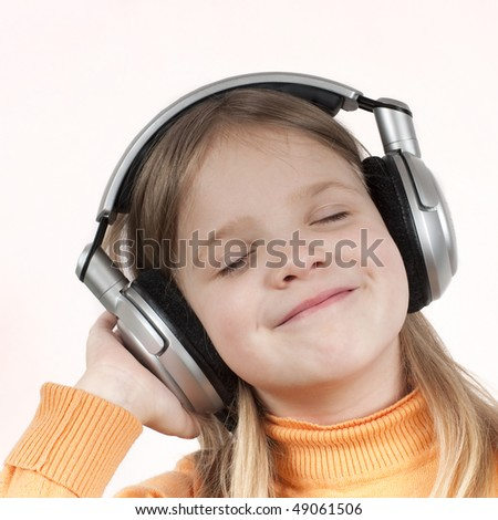 Little girl enjoys music wearing hi-fi headphones