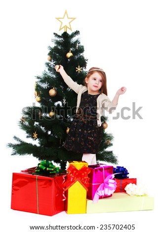 Little girl enjoys standing at the Christmas tree.White background, isolated photo. - stock photo