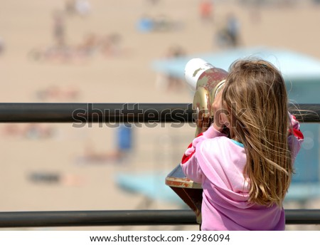 Little Girl Enjoys View of Beach Through Telescope - stock photo