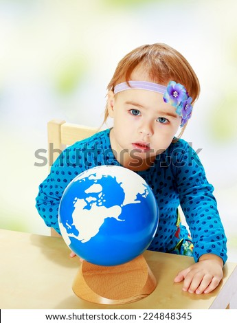 Little girl examines the globe.Happiness, winter holidays, new year, and childhood. - stock photo