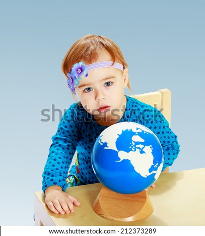 little girl examines the globe in the Montessori classroom on a blue background.the concept of a happy childhood, education of children, teens - stock photo