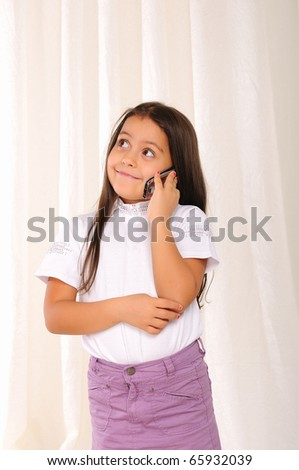 little girl excitedly chatting with someone on the phone - stock photo