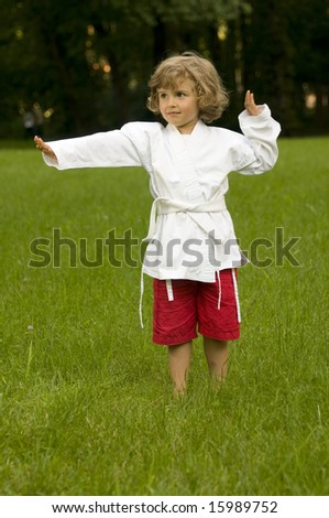 Little girl exercising in the garden