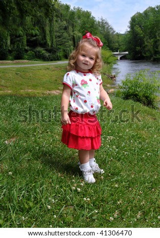 Little girl explores the banks of the Doe River in Tennessee.  She is standing on the grassy banks above the water. - stock photo