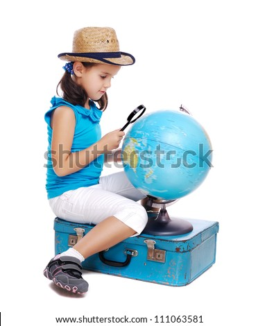 Little girl exploring a globe  with a magnifying glass sitting on a blue suitcase - stock photo