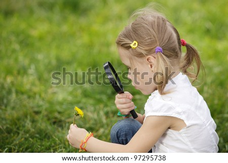 Little girl exploring the flower through the magnifying glass outdoors - stock photo