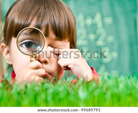 Little girl exploring the grass - stock photo