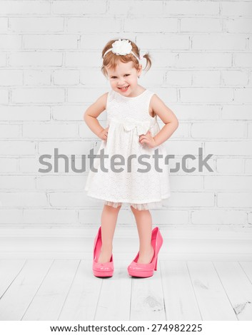 little girl fashionista in her mother's big pink heeled shoes - stock photo