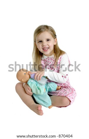 Little Girl Feeding a Baby Doll - stock photo