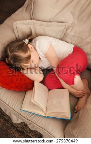 Little girl felt a sleep while reading a book in chair - stock photo
