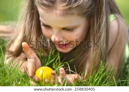 Little girl find easter egg outdoor. Face close up. - stock photo