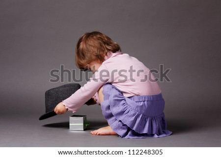 little girl finding surprice under magic hat - stock photo