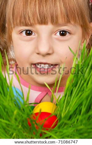 Little girl finds a multicoloured easter eggs in the tall green grass - stock photo
