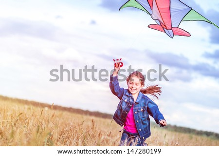 little girl flies a kite in a field of wheat - stock photo