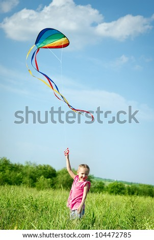 Little girl flying a kite in the field - stock photo