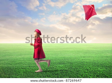Little girl flying a kite on a green meadow - stock photo