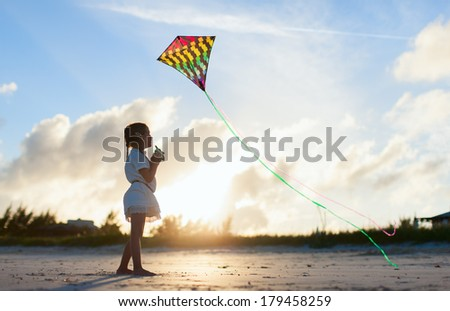 Little girl flying a kite on beach at sunset - stock photo