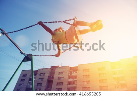 Little girl flying on swing in city house yard. Childhood, Freedom, Happy, Summer Outdoor - stock photo