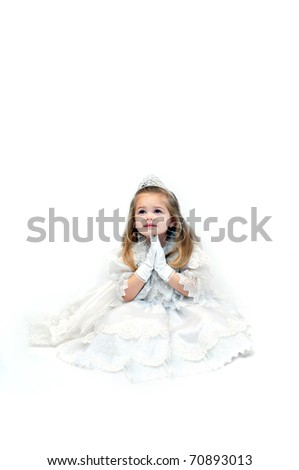 Little girl folds her hands in prayer.  She is sitting in an all white room and wearing an all white pageant dress and crown.