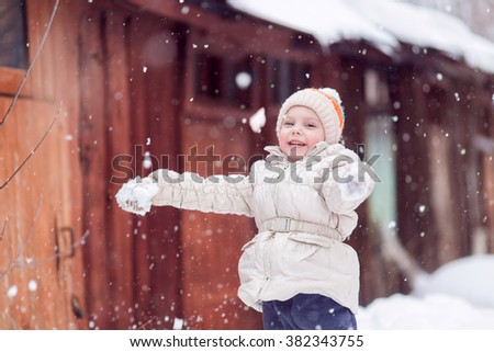 little girl four years on the street in winter white jacket catches snowflakes flakes and rejoices, smiles - stock photo