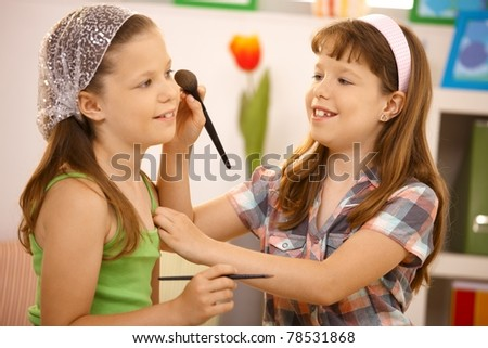 Little girl friends having fun with makeup at home, smiling.?
