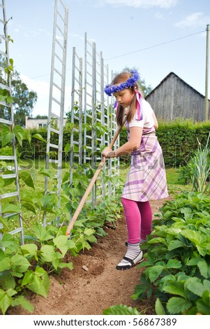 Little girl gardening, weeding a planting bed