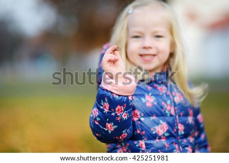 Little girl gathering acorns for crafting and playing on beautiful autumn day outdoors